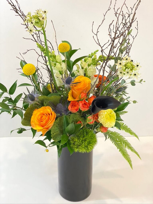 Branching Out This late summer floral has height and stature in a sleek black glass vase. Branches, seasonal flowers and dried mushrooms are part of the beauty you'll find here. Seattle flower delivery by Juniper Flowers