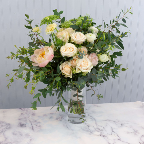 Hand tied wedding bouquet in white and blush with lush natural foliage