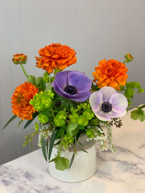 Cream toned glazed pottery with an unglazed sand colored lip. Brightly toned Spring flowers such as ranunculus and anemones, euphorbia and accenting foliage