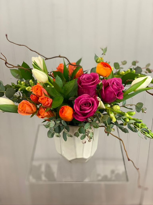 This floral is a vibrant display of orange and pink with a subtle touch of creamy white to bring out the color of the geometric sided pottery vase. This cheery floral is great for a birthday, anniversary, sympathy, new baby, or simply to say I'm Thinking of You. Tulips, roses, and spray roses are the focal flowers included for Seattle flower delivery by Juniper Flowers