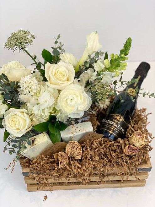 Get Hitched Gift Crate consists of a lovely white floral with 2 handmade soaps, dried flowers and a bottle of champagne. Choose from a half bottle of bubbles to a mid or higher priced bottle. Seattle flower delivery by Juniper Flowers