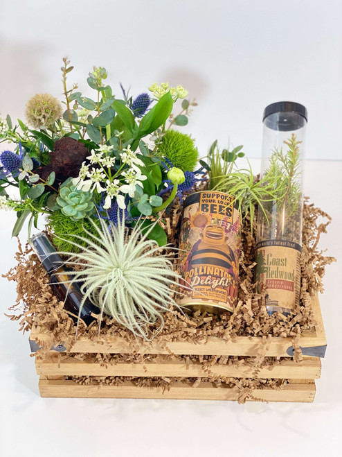 Our Earth Day gift crate is filled with fun items good for the environment. Featuring a mini version of our forest floor arrangement consisting of all local flowers and foliage, a packaged live tree start, seed grow kit of wildflowers that support bees, butterflies and other pollinators, several air plants and a glass mister bottle.