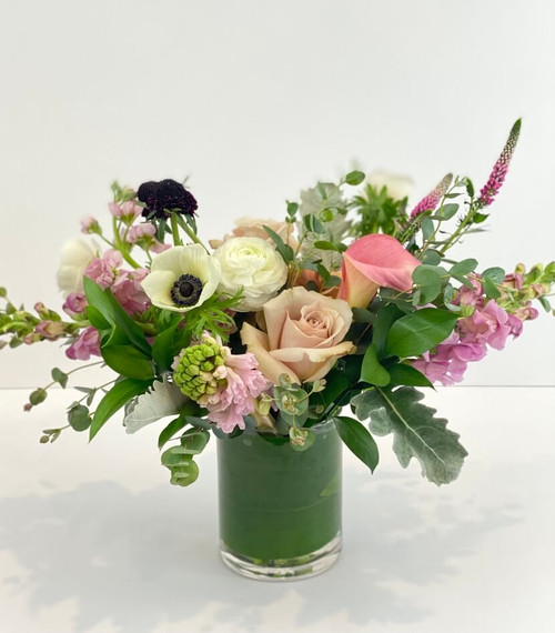 Adore Me This floral is a fun burst of subtlety with its pastel blush pinks, creamy white and hints of berry tones. This comes in a clear glass vase with leaf wrapped inside to conceal the stems and is available in many price ranges. Seattle flower delivery by Juniper Flowers