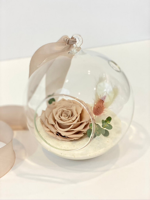 Everlasting Memories  This lovely little glass globe has white sand and a stunning preserved rose in a sandy blush/beige tone. We add a delicate touch of dried eucalyptus and bunnytail, finishing the look with a pale blush silk ribbon. A perfect reminder of someone special in your life or to remember someone you've lost. Seattle flower delivery by Juniper Flowers