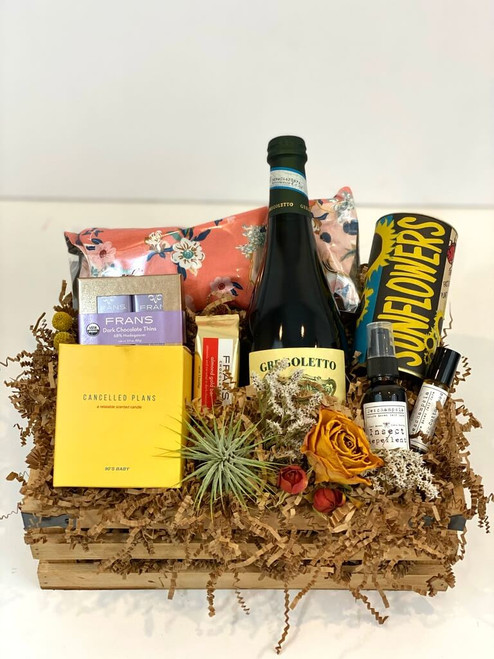 Sun Break Gift Crate Take a summer break and gift yourself or a loved one this customized crate. Included in it is a Cancelled Plans scented candle, air plant, dried flowers, ready to plant Sunflower Seed Kit, relaxing lavender flaxseed eye pillow, insect repellant, rollerball natural fragrance, and assorted Fran's chocolates. Choose the best bottle of wine or champagne for your occasion! (Pictured in this crate is Gregoletto Prosecco)Seattle Flower and gift crate delivery by Juniper Flowers