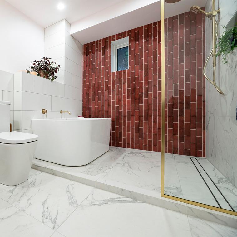 Marble look bathroom with burgundy subway tile