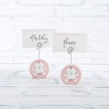 """Baby Girl Pink Place Card Holder (Set of 6)  Kate Aspen's Pink Baby Girl Place Card Holder in a set of 6 is the perfect way to bring a touch of style to your shower right from the start!  Each set comes equipped with 6 matching cardstock place cards, so your holders are ready to use when you need them.  Made from resin, the place card holders are built to last as cute baby shower souvenirs as well!     Features and facts:  Round resin baby pink place card holder with white and pink cardstock place card. Measures 1.33""""w x 2.44""""h x 0.27""""d, place card measures 2.16""""w x 1.22""""h x 0.03""""d Sold in sets of 6"""