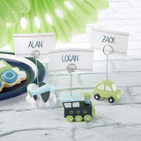 """Precious Cargo Transportation Place Card Holder - Assorted (Set of 6)  With planes, trains, and automobiles, you can direct your guests just where to go in a fun and adorable way using Kate Aspen's Precious Cargo Transportation Place Card Holders!  For baby showers or birthday parties large and small, these place card holders are sold in sets of 6 and come equipped with cardstock place cards ready to be adorned with the names of all of those sharing your special day.  Each little Precious Cargo Transportation Place Card Holder is made from sturdy and lightweight resin, making them delightfully simple to transport to and from your venue!  Features and facts:  Blue, green, and white resin place card holders in airplane, train, and car shapes Includes coordinating place cards Airplane place card holder measures 1.8"""" w x 2.9"""" h x 2"""" d; car place card holder measures 1.7"""" w x 3.3"""" h x 1"""" d; train place card holder measures 2"""" w x 3.3"""" h x 0.9"""" d Sold in sets of 6"""