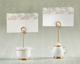 """Tea Time Whimsy Place Card Holder (Set of 6)  Kate Aspen's Tea Time Whimsy Place Card Holders, available in sets of 6, add a delightful touch to your tea party table decor. Each set of place card holders comes with 3 teapot and 3 teacup shaped bases—all crafted with sturdy resin—to keep the matching floral place cards upright for all to see.  Features and facts:  White teapot- and teacup-shaped place card holders with gold foil details. Included place cards feature a pink floral design on a white background. Metal spiral stem holds place cards securely in place. Each set of 6 includes 3 teacup and 3 teapot shapes Teapot Place Card Holder: 0.98"""" x 1.73"""" w x 2.99"""" h Teacup Place Card Holder: 1.29"""" x 1.65"""" w x 2.75"""" h Card: 0.03"""" x 2.51"""" w x 1.49"""" h"""