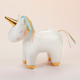 """Unicorn Porcelain Bank A bank that is not only functional but beautiful is as rare as, well, as a unicorn! Baby Aspen has combined the two to make a unique baby girl shower gift. Our Porcelain Unicorn Bank is suitable for baby's first coin bank, but is also a beautiful decorative piece that can brighten up her nursery.  Features and facts:  White Porcelain unicorn bank is adorned with a gold foil horn and hooves, along with a mane and tail made of pink, aqua and gold ribbons Bank is hand wash only Measures 8.7"""" w x 3.5"""" d x 8.3"""" h"""