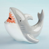 """Shark Porcelain Bank Chomp chomp! Our Porcelain Shark Bank allows your little ones keep their pennies safe and sound. If you're looking for a unique gift or a shark themed gift for a baby shower or birthday party, we've got you covered!  Features and facts:  Gray Porcelain coin bank shaped like a shark, featuring white teeth and a money slot in the mouth of the shark 100% Porcelain bank is hand-wash only Measures 8.9"""" w x 8.7"""" d x 7.4"""" h"""