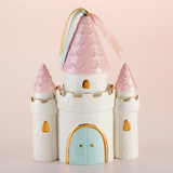 """Simply Enchanted Castle Porcelain Bank A decor item and unique Porcelain bank that truly has no equal, Baby Aspen's Simply Enchanted Porcelain Castle Bank pulls double duty. Not only does it keep baby girl's trust fund safe and sound, it's a lovely décor piece that will definitely coordinate with any nursery theme.  Features and facts:  White castle-shaped Porcelain bank features three towers with pink tops, light blue castle doors, and gold detailing. The tallest tower is topped with three satin ribbons in pink, mint, and gold Hand wash only, 100% Porcelain Measures 7.3"""" w x 4.1"""" d x 10.2"""" h"""
