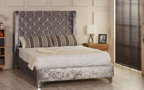 Riga Wing Back upholstered bed frame shown in ice crush velvet fabric with diamante button and chrome  feet. The Esupasaver Bed Company Quality Beds Made in England