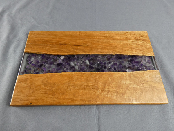 """Maple Small Amethyst Serving Board #12 This is a solid birdseye maple charcuterie serving board filled in the center with amethyst chips and epoxy.   The board is about 7 ½"""" wide, 12"""" long, and 1/2"""" thick.  This was finished with food safe cutting board oil and a protective cutting board wax."""