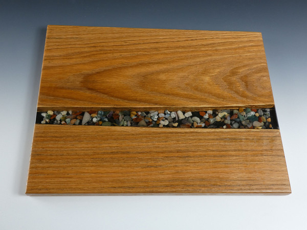 """Oak River Pour Serving Board #13 This river pour style charcuterie serving board has solid oak on both sides and smooth stones set in clear epoxy in the center.   The charcuterie board is about 11""""wide, 14""""long, and 5/8"""" thick."""