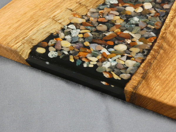 """Oak River Pour Serving Board #16 This river pour style charcuterie serving board has solid oak on both sides and smooth stones set in clear epoxy in the center.  The charcuterie board is about 11""""wide, 14""""long, and 5/8"""" thick."""