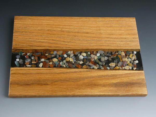 """Oak Small River Pour Charcuterie Serving Board #20 This charcuterie serving board is made from solid oak. Small stones and epoxy resin were added to the center to create a river pour effect.   The charcuterie board is about 7 1/2"""" wide, 12"""" long, and 5/8"""" thick.   It is finished with food safe cutting board oil and protective cutting board wax."""