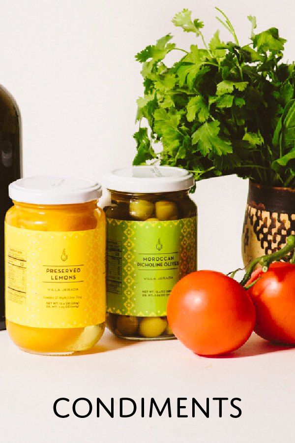 Preserved lemons and olives in a jar with tomatoes on the side and parsley