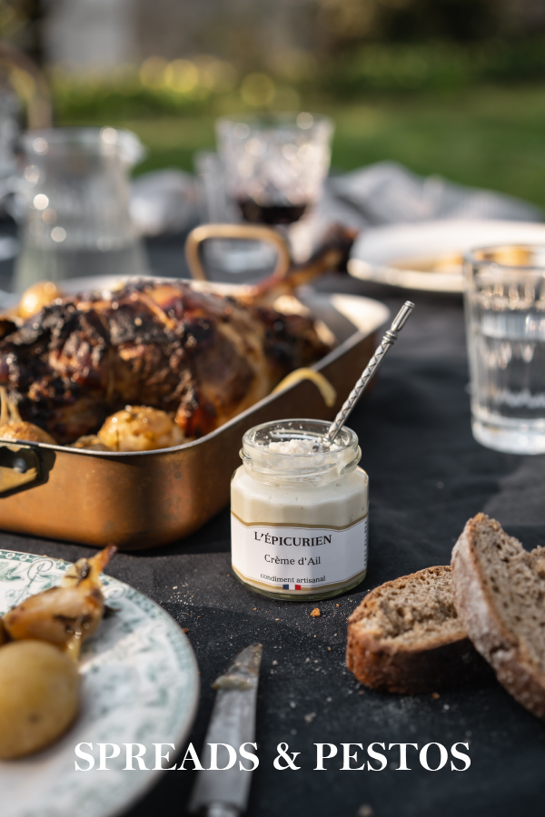 Garlic cream on an outdoor table next to a roasted chicken and bread ready to be eaten