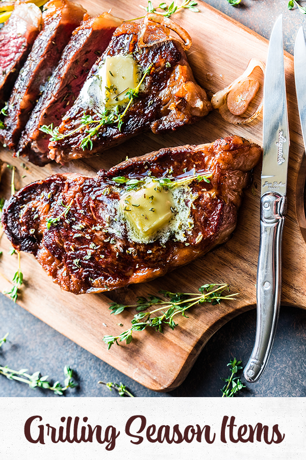 Grilled meat on wooden board with steak knives and herbs