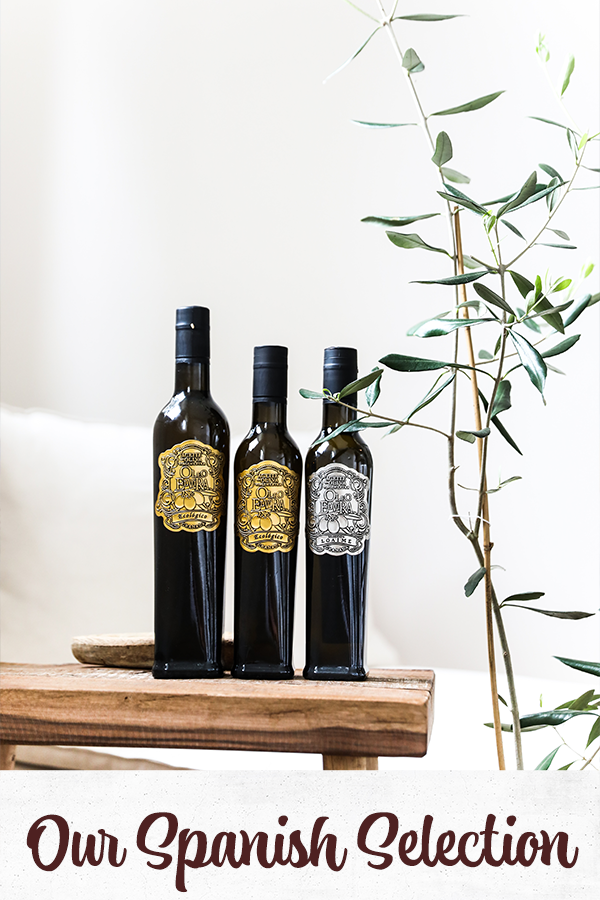 Spanish Olive oils on a wooden bench with an olive tree