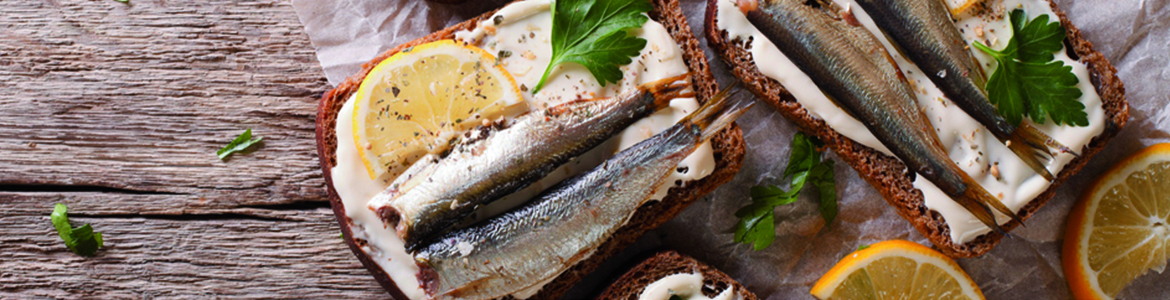 sardines on toast with lemon slices and fresh herbs