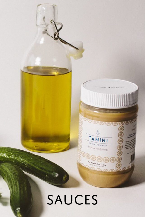 Tahini sauce from Morocco next to a bottle of olive oil and two cucumbers