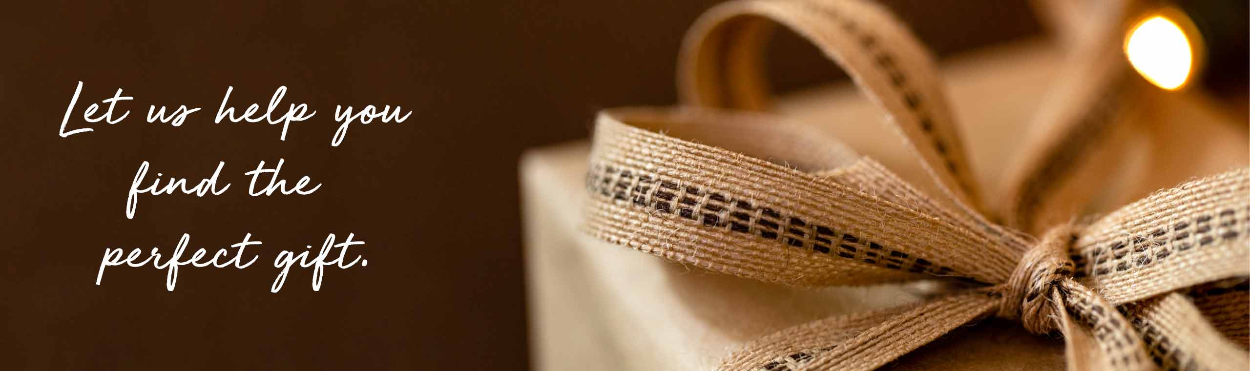 Let us help you find the perfect gift. Gift wrapped in brown paper with a woven brown ribbon.