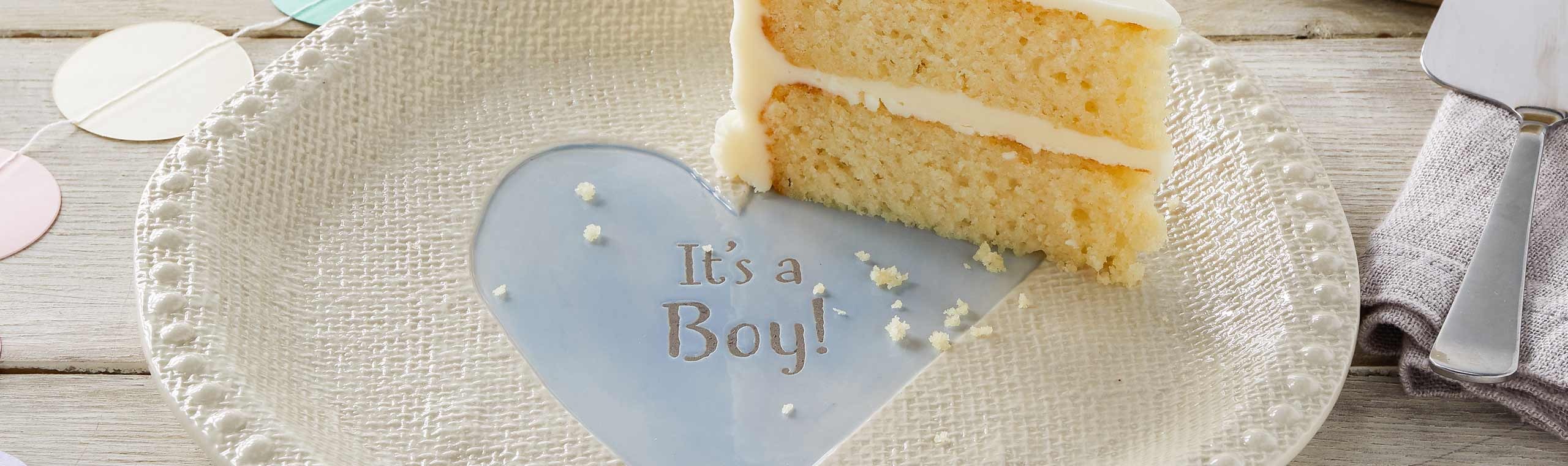 Piece of cake on textured ceramic plate decorated with blue heart with the words It's a boy