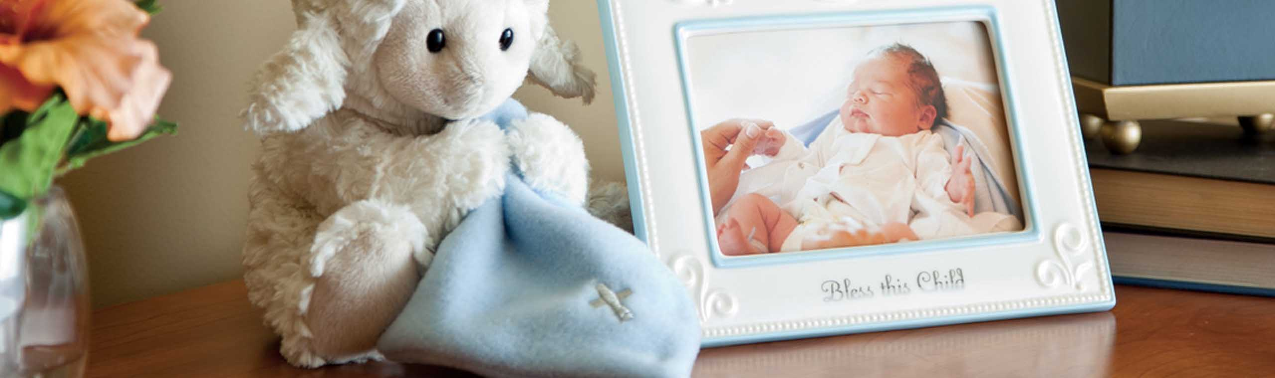 White lamb stuffed animal holding a blue blankie with embroidered cross next to white picture frame of baby