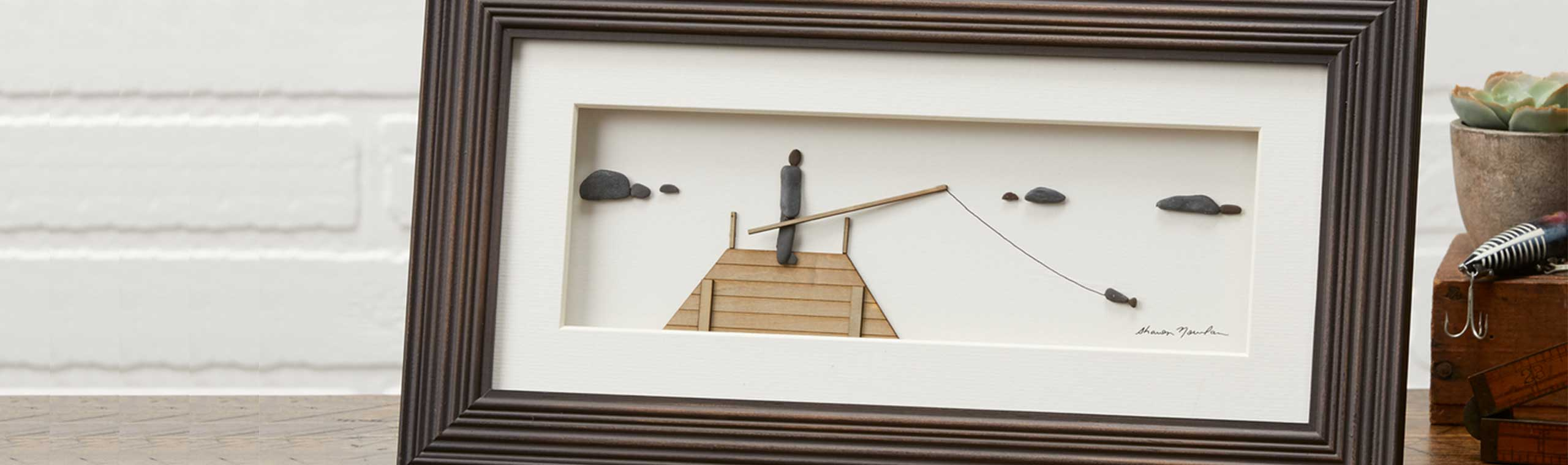 Wood-framed pebble art of man fishing off a dock