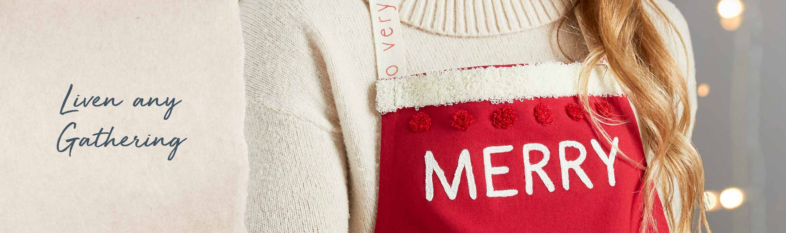 Liven any gathering. Woman wearing a red apron embroidered with the word MERRY