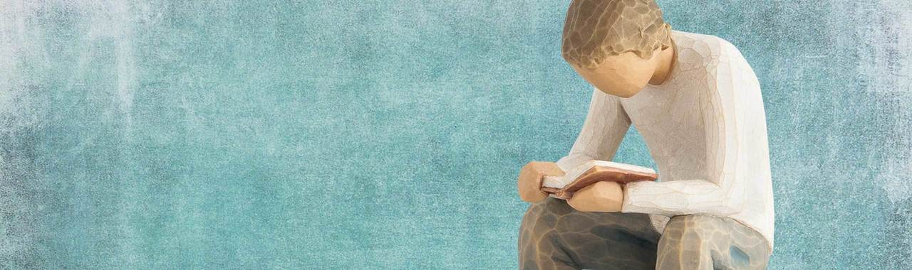 a figurine of a boy reading a book on a watercolor background