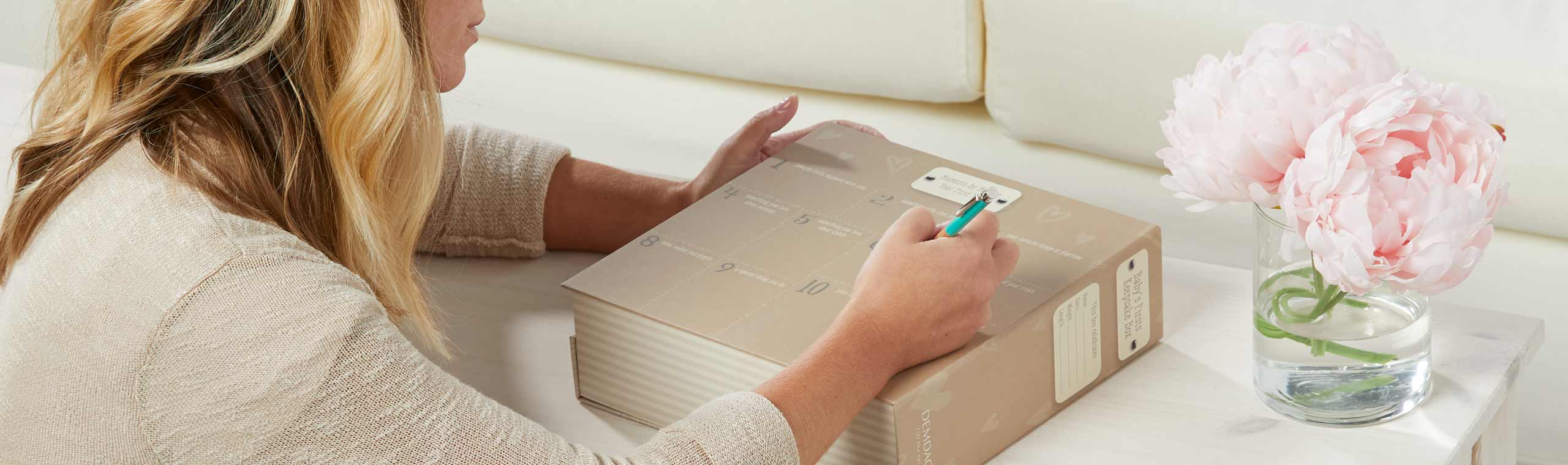 Young mom writing on keepsake journaling box in living room