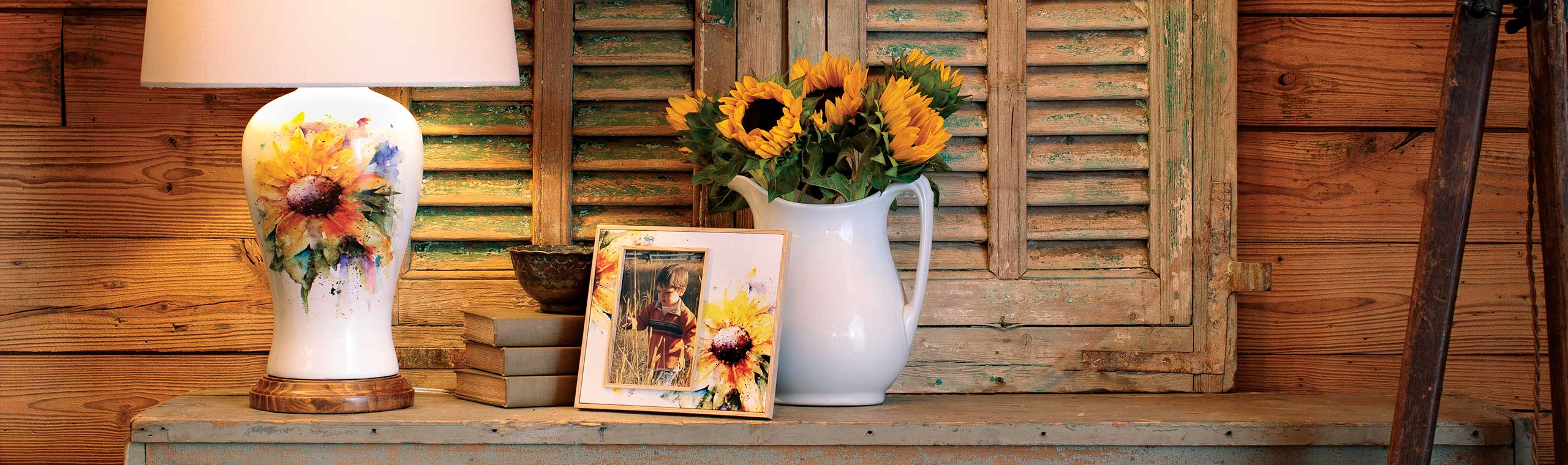 Large white table lamp with bright yellow sunflower watercolor artwork sitting on rustic table