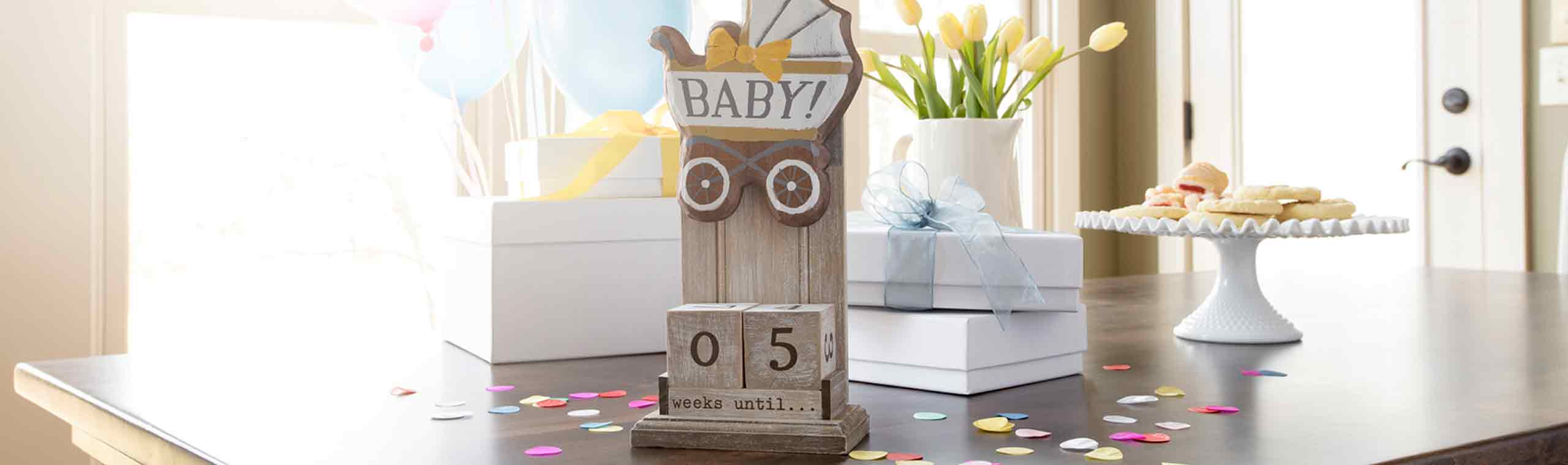 a mark the moment stand with a stroller token and wooden blocks marking the date for the new baby.