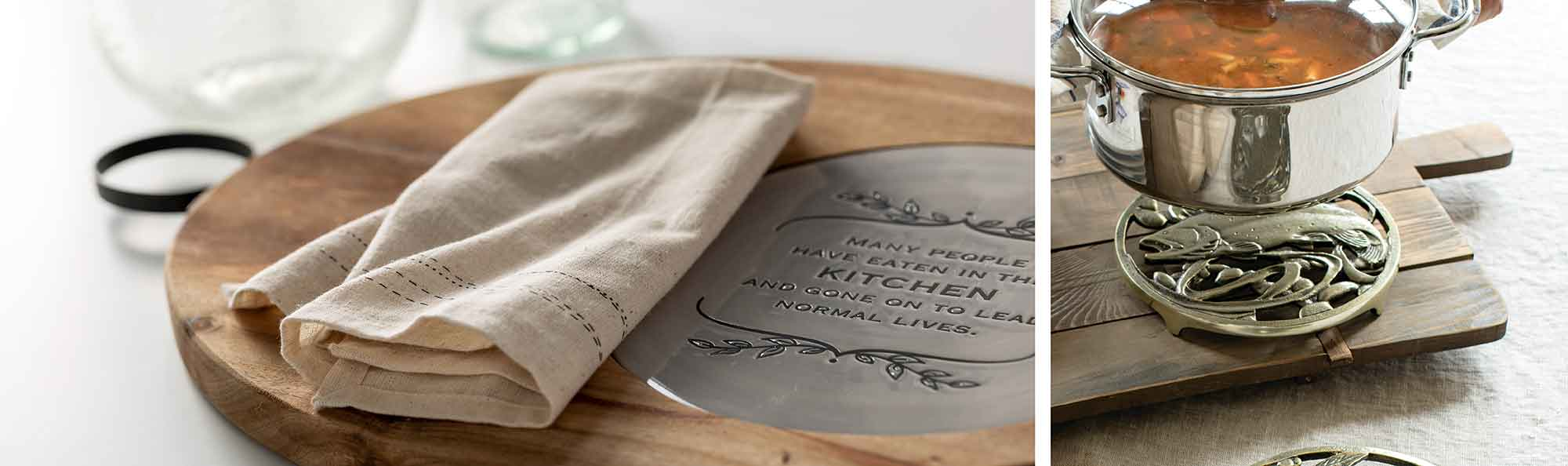 hot pan setting on a metal Trivets with a quote about the kitchen and another with design of a fish