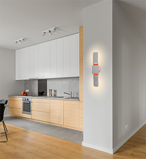Spire moving wall sconce light by furl mounted in a dining room shown in the open and expanded position with orange RGB light and white Back lighting.