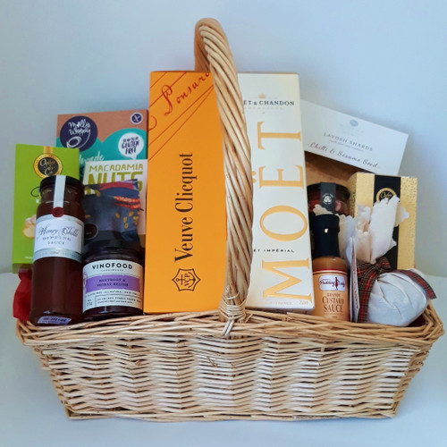 This hamper is a foody's delight packed with gourmet items and complimented with Moet &  Veuve Champagnes