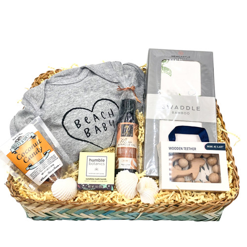 beach themed baby gift basket with a cute baby onesie jumpsuit that says Beach Baby, a bamboo swaddle with sea turtles, a wooden turtle teether, tamanu oil, humble botanics pure love bath bomb, hawaiian heritage farms coconut candy