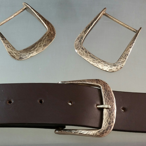 The Farrier Square buckle in bronze with a hammer textured, satin finish.  This heavy bronze buckle fits 1 1/4 inch belts.