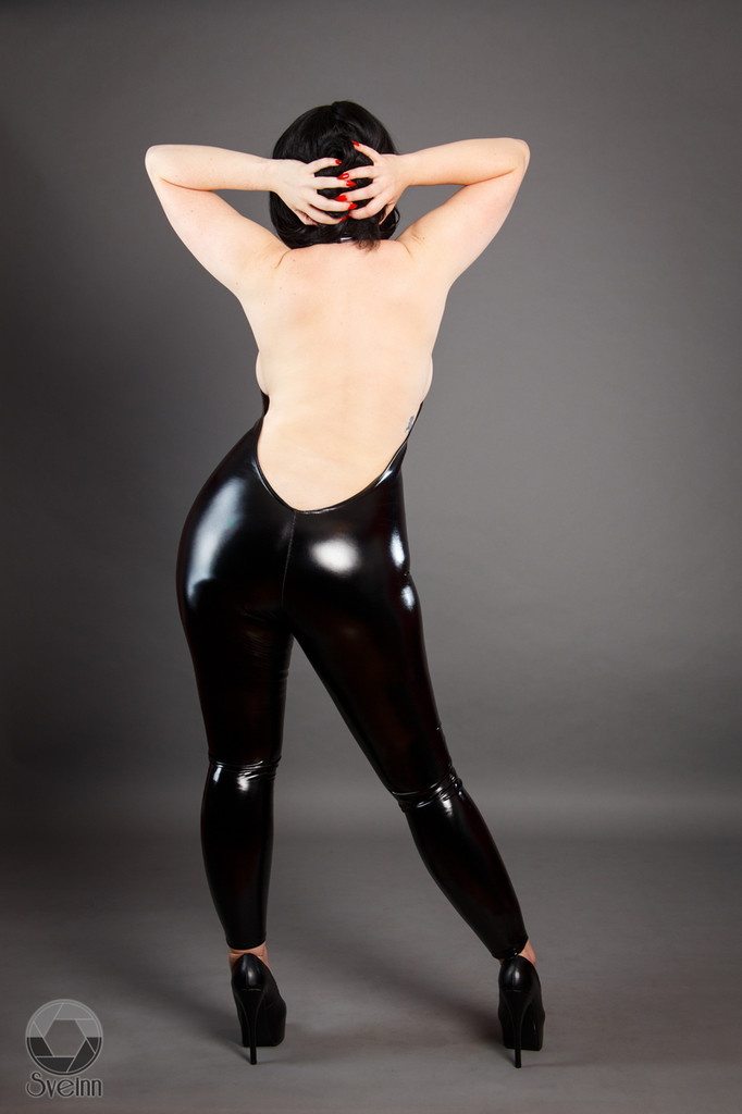This sleek catsuit glides over the body like a deceptively comfortable glove, revealing a beautiful spine and arms while concealing the chest and neck.  Featured in this image:  2 inch collar Open back Gloss Black 4-way stretch vinyl (Available in all fabrics) Photo by Meg Schutz.  SKU: CS3 Price: $175.00