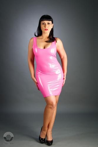 Vinyl/PVC Mini Dress by Mister Pierre  Accentuating cleavage and natural curve on a female or feminizing a masculine frame, this mini dress can be seen keeping to the outskirts of the crowd observing a scene or holding to every collared curve and representing presentation and daring.  Made custom to your measurements from Mister Pierre.  Featured in this image:  Tank Style. Gloss Hot Pink 4-way stretch vinyl (Available in all fabrics). Aluminum on black separating zipper.  SKU: DR3 Price: $50.00