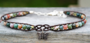 Fancy Jasper stones threaded onto chocolate brown leather. Leather features a focal celtic design and silver plated butterfly charm. Silver plated lobster clasp and jump rings make this choker adjustable to size.