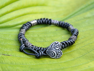 Metallic grey leather knotted with dainty heart cut out silver beads. Bracelet has 2 button holes to fit either 6 1/2 in or 7 1/4 in sized wrist and closes with a silver pewter heart shaped button