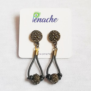 Gun Metal leather with Antique Brass beads. Titanium posts for metal sensitive ears. Hangs 2 inches in length.