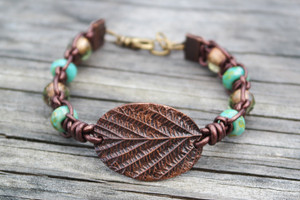 Copper leaf focal point framed with metallic brown leather cords knotted with turquoise and olive roller beads. Antique brass lobster clasp and jump rings create and adjustable fit.