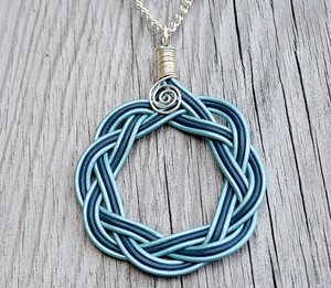 Pastel blue and Indigo blue leather intertwined into a 3 inch celtic circle pendant. Silver plated chain measures 20 inches in length.