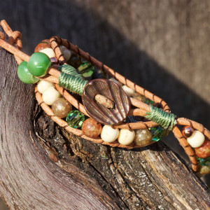 The handmade double wrapped bracelet has Autumn Jasper and natural bone beads. Detailed with sparkling peridot green Swarovski crystals, the bracelet ends with a shell shaped copper plated button. The bracelet is 16 inches in length and fits a 6 1/2 inch wrist.