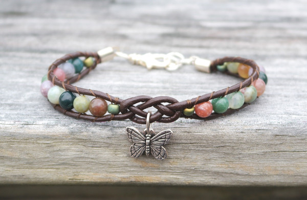 Fancy Jasper stones threaded onto chocolate brown leather. Leather features a focal celtic design and silver plated butterfly charm. Silver plated lobster clasp and jump rings make this bracelet adjustable to size.